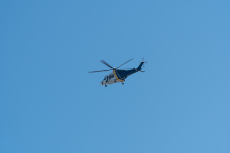 Generic blue and white police helicopter with visual camera surveillance equipment fly in sky high above city aerial patrol