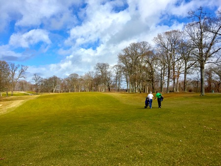 Two golfing friends walk down the fairway on a golf course on a beautiful winter day. Warm winter temperatures allow for cold weather games. Stock Photo
