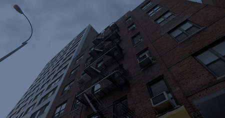 Exterior photo NYC style apartment building above store front awnings at night. Vertical look up to windows and fire escape on facade