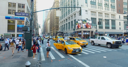 New York City, Circa 2017: Busy commuter traffic and people overhead view Manhattan intersection. Man hails yellow taxi cab travel to office