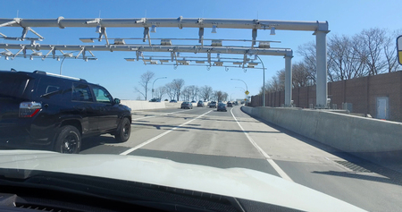 POV driving forward view passing highway cashless toll plaza sensors before crossing suspension bridge in New York City.