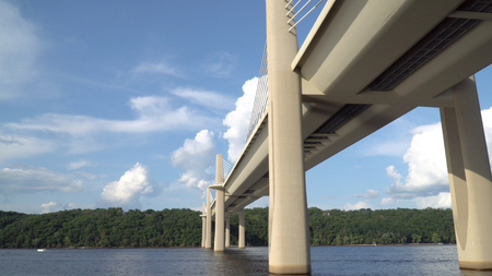 View from boat passing underneath bridge spanning over a river on a clear summer day. Modern construction engineering for road motorway to cross natural borders Stockfoto
