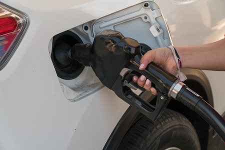 Female hand holds gas station fuel nozzle pumping gas into white car tank for power to drive