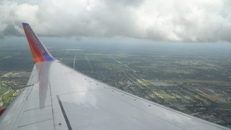 Florida, USA - Circa 2017: Southwest airlines Boeing 737 airplane wing painted business logo on wingtip. View over wing on decent to airplort ground blelow Editorial