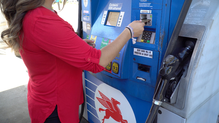New York, USA - Circa 2018: Unidentifiable woman in red shirt swipe credit card into Mobile gas station fuel pump to pay for gasoline to fill car tank