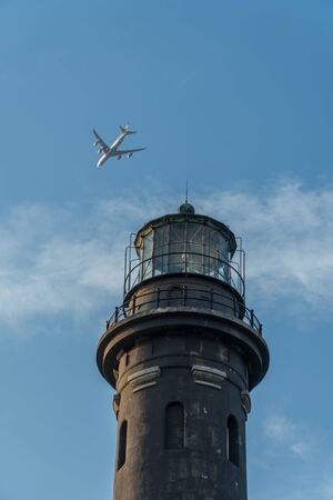 Flying passenger jet airplane passes over lighthouse monument on clear summer day past blue sky and clouds. Light houses used for aviation and maritime navigation with circular strobe spot light