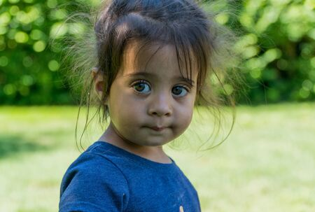 A young adorable female toddler girl looking past camera with innocent smile and big wide beautiful eyes outside in backyard during summer time. Multiple concept usage for model released photo