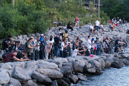New York City, Circa 2019: A large group of photographers organize photo walk to capture pictures on digital cameras along rock shore line waiting for sunset and golden hour photographs