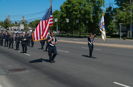 Long Island, NY - Circa 2019: Memorial day parade celebration, EMS and fire fighters march in uniform down street to honor USA military service in summer time festivities