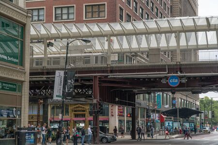 Chicago, USA - Circa 2019: Elevated train in downtown Chicago stop at station platform during morning rush hour commute.