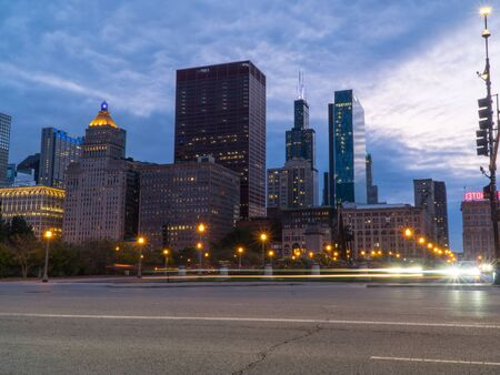 Chicago skyline looking past a busy downtown road at night with car traffic light trails passing through intersection long exposure