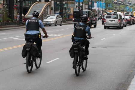 Chicago, USA - Circa 2019: Chicago PD officer on bike patrol riding on downtown street