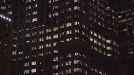 Generic night time establishing shot of typical apartment or office building in the dark. NX exterior of building with illuminated windows from inside