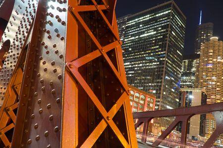 Night time detail shot of bridge overpass steel support columns with urban city skyline illuminated in background 免版税图像