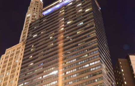 Chicago, IL - Circa 2019: Night time exterior establishing shot photo of a big city downtown apartment or office building illuminated to light up skyline 免版税图像