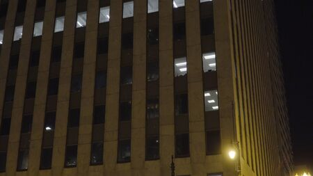 Night time exterior establishing shot of a generic apartment or office building facade with some lights on in a few windows. Business working after hours