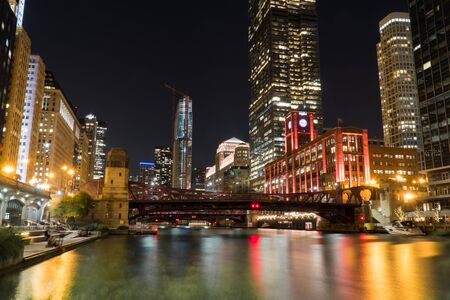 Night time exterior establishing shot overlooking Chicago river front area with skyline illuminated in dark sky reflecting off water in beautiful scene 免版税图像