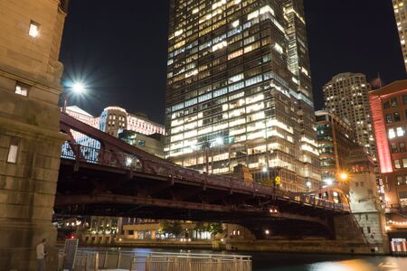 Beautiful night time establishing shot view of downtown Chicago bridge over river front walk with tall skyscraper buildings in background illuminating dark sky with window lights over busy roadway