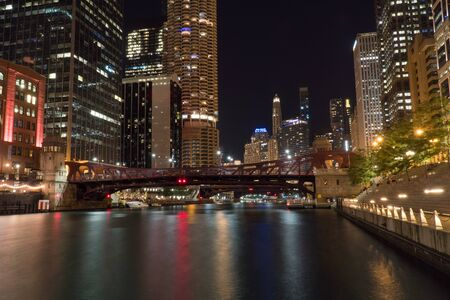 Chicago, USA - Circa 2019: Night time over of Chicago river skyline at night with hotels and luxury apartment and office buildings in background filling cityscape 免版税图像
