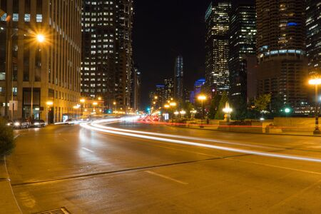Night time long exposure of generic busy downtown city urban street with car light trails traveling down highway through metropolis intersection, skyline in background