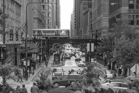 Chicago, IL, USA - Circa 2019: Day time exterior view of downtown Chicago city street between skyscraper buildings as L train passes overhead morning rush hour traffic. Black and white retro photo