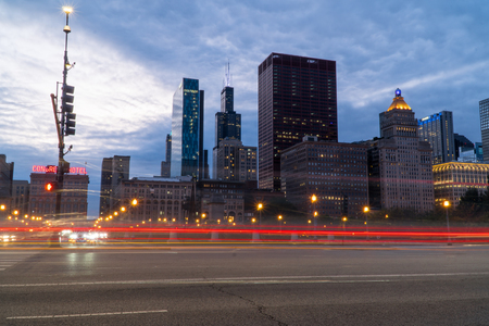 Chicago, IL - Circa 2019: Night time establishing shot of downtown Chicago skyline long exposure light trails of cars passing through busy intersection surrounding city. 新闻类图片