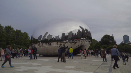 Chicago, USA - Circa 2019: Famous cloud gate art sculpture in downtown park made of steel reflecting cityscape skyline on Chicago bean