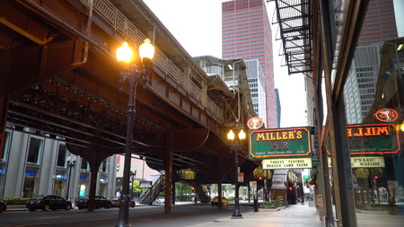 Chicago, USA - Circa 2019: Day time exterior Millers Pub in downtown Chicago under the L train tracks over street level. Color over sign for generic usage 新闻类图片