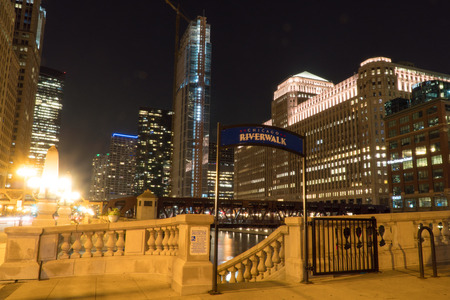 Chicago, USA - Circa 2019:  Riverwalk sign entrance at night with luxury hotel apartment building in skyline illuminated in background