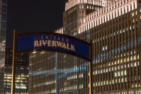 Chicago, USA - Circa 2019:  Riverwalk sign closeup at night with luxury hotel apartment building in skyline illuminated in background