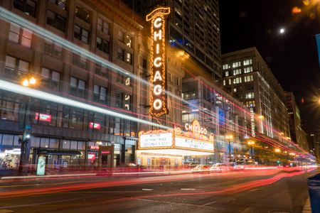 Chicago, IL - Circa 2019: Chicago landmark theatre famous venue in downtown. Night time exterior establishing shot long exposure of traffic light trails passing marquee lit up logo sign 新闻类图片