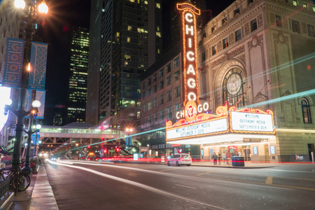 Chicago, IL - Circa 2019: Chicago landmark theatre famous venue in downtown. Night time exterior establishing shot long exposure of traffic light trails passing marquee lit up logo sign 報道画像