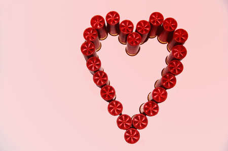 Shotgun shells in heart shape with pink background