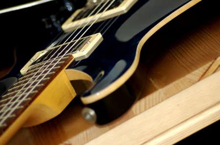 木製の椅子の上のギターのピックアップに焦点を当ててください。