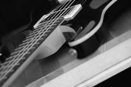 椅子の上の黒と白のギターはピックアップに焦点を当ててください。