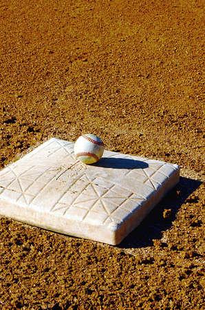 backstop: Baseball sitting ontop of base in stadium. Stock Photo