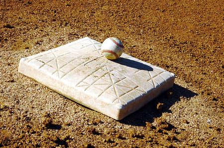 bases: Baseball sitting ontop of base in stadium. Stock Photo