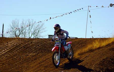 dirt bike: Dirt bike rider just landing jump in race.