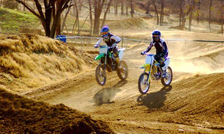 dirt bike: Two dirt bike riders down the long stretch. Stock Photo