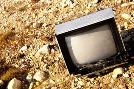 Broken television in field Stock Photo
