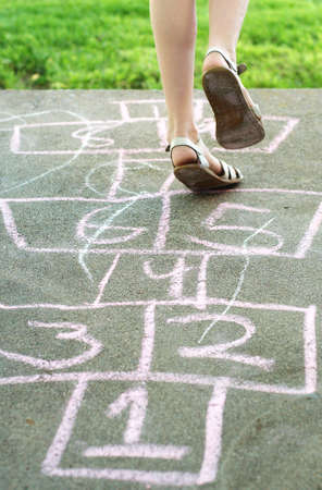 hopscotch: Little girl playing in backyard Stock Photo
