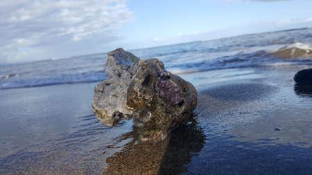 Rock on sandy beach Stock Photo