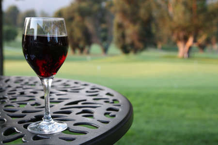 Glass Of Red Wine On Iron Table With Golf Course In Background