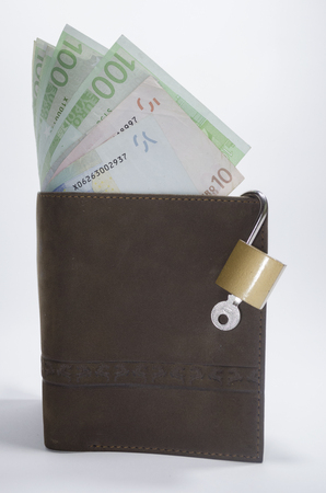 Wallet with curencies and padlock as a concept of savings photo
