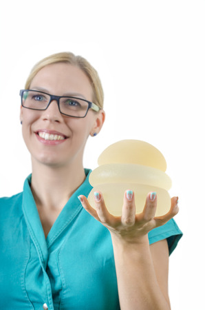 Silicone breast implant. Doctor hold silicone breast prothesis.