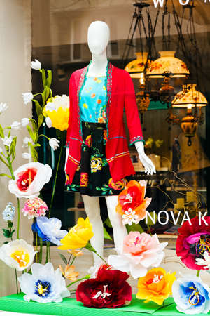 Boutique window with mannequin surrounded by flowers