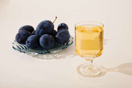 Small glass of rakija, with plate full of plums, on white background Stock Photo