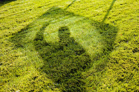 Abstract image of lawn with shadows of man and a billboard