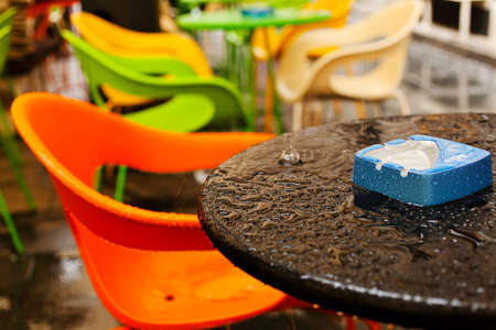 View of wet table with blue ashtray on it and empty orange chair