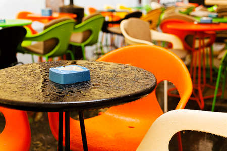chairs: Table and chairs at a sidewalk cafe after rain; note shallow depth of field